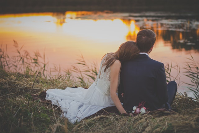Wedding Couple Sitting In Front Of Water At Sunset